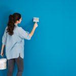 Mulher pintando a parede de azul