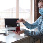 Mulher de máscara limpando as mãos com alcool em gel, sentada na mesa de trabalho.